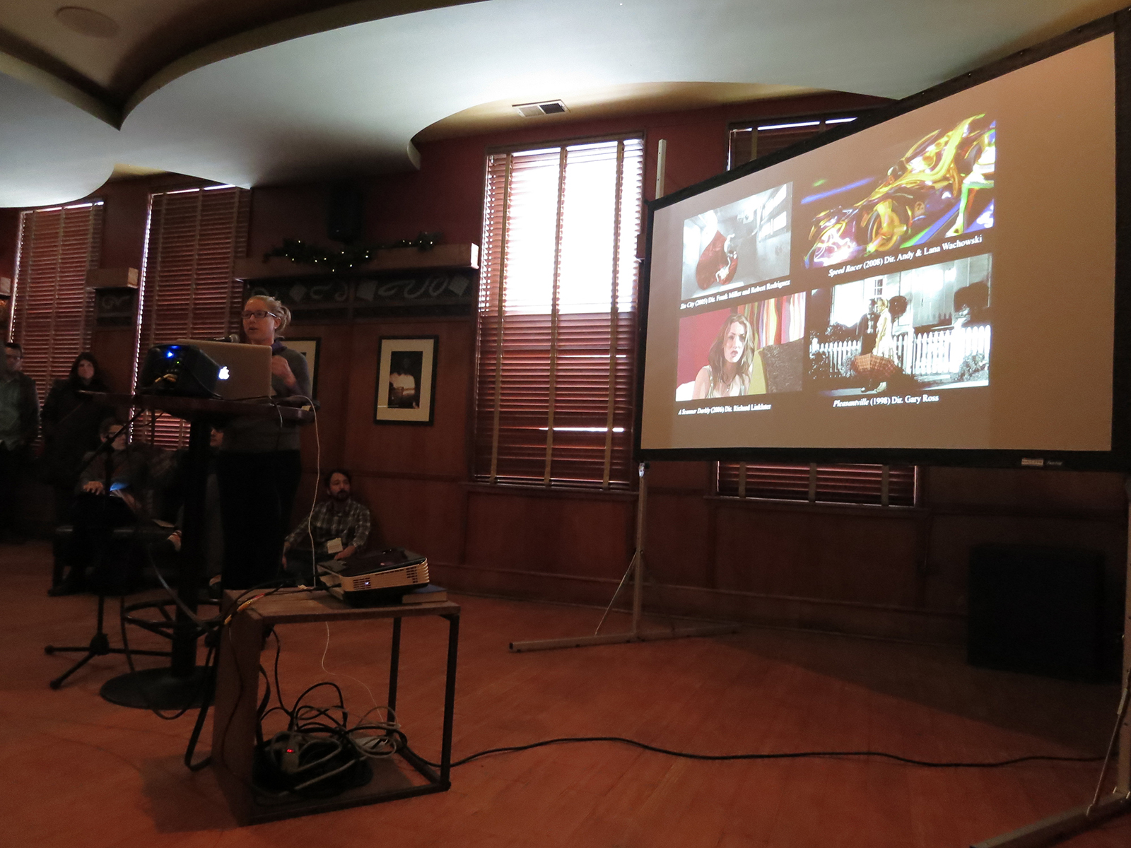 Carolyn Kane explaining the Photoshop Cinema at NMC Lightning Talks, Bar Louie, 2014, ©Pat Badani. (Used with permission.) 02-Kane-lightning-2014
